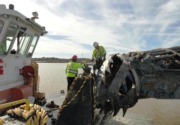 Workers replace teeth on the cutter on the floating dredge
