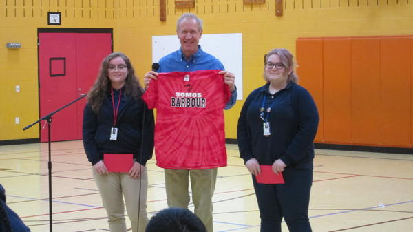 Gov. Rauner recieving a spirit t-shirt from the heads of Barbour's student council.