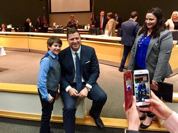 Sixth grader Ethan Greenberg poses with Senator Jeff Brandes, sponsor of SB 104, at a senate education committee hearing in February, as his mother looks on.