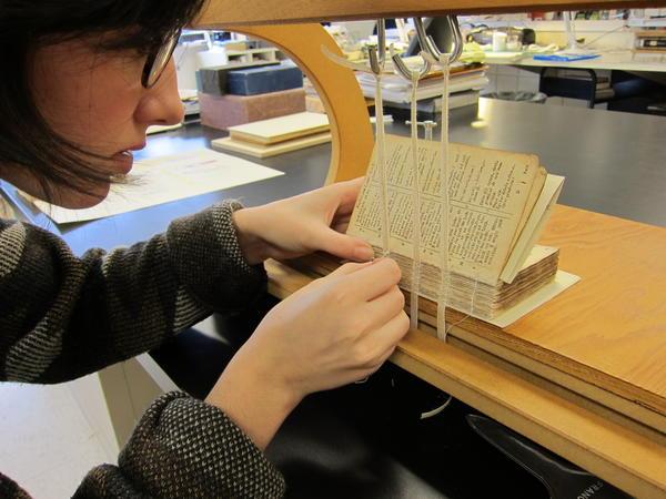 University of Michigan Library conservation intern Allison Donnelly resews an eighteenth-century book.