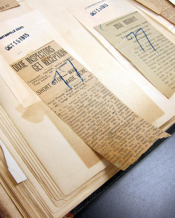 The repair of a 1915 newspaper clipping in a scrapbook documenting the construction of the Dixie Highway at the University of Michigan Library conservation lab.