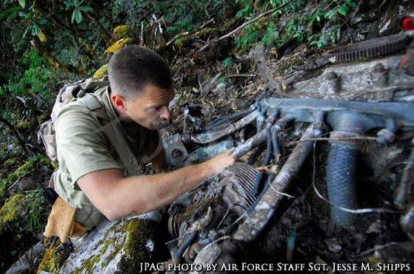 Peter Janse of the Joint POW/MIA Accounting Command examines one of the engine of the B-24 Hot as Hell in Arunachal Pradesh, India in 2008.