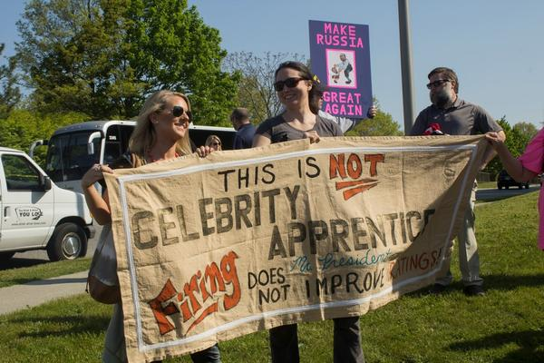 Two women hold their homemade sign referring to Trump's television show, The Celebrity Apprenctice.