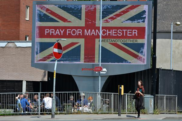 A woman walks past an electronic advertising board displaying a Union flag and the words 'Pray For Manchester'.