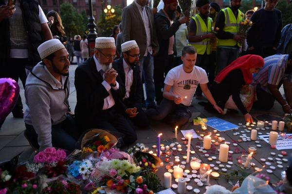 People pray and light candles in Albert Square in Manchester, England, in solidarity with those killed and injured in the May 22 terror attack at an Ariana Grande concert at the Manchester Arena. Twenty-two people died and dozens were injured in Britain's deadliest terror attack in over a decade after a suicide bomber targeted fans leaving the concert.