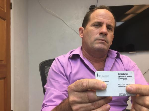 Javier Vivo with his health benefits card he received through work at Miami International Airport.