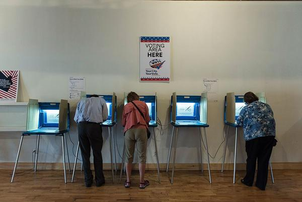 Three people vote in booths at the Early Vote Center in Minneapolis on October 5, 2016.