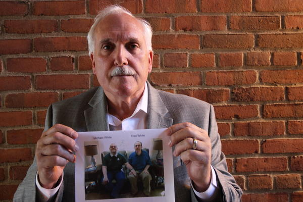 Robert White holds a picture of his sons Fred, 46, and Michael, 32, who are both on the autism spectrum.