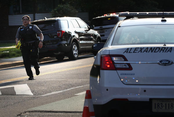 A member of the Alexandria police force runs near the scene of a shooting in Alexandria, Va.  Senior Republican Congressman Steve Scalise was among several victims shot and wounded at a morning  baseball practice ahead of an annual game between lawmakers. Scalise is the majority whip who rallies Republican votes in the House of Representatives.