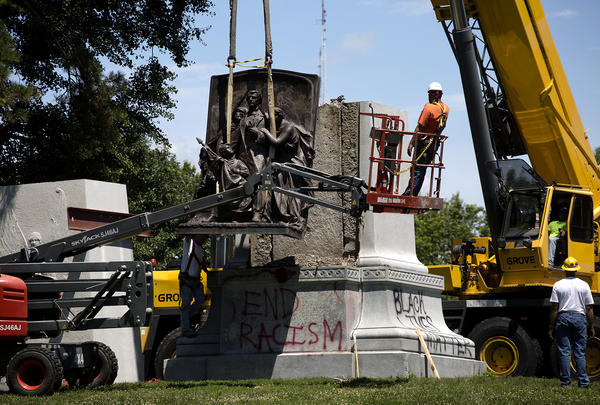 A crew removes a bronze sculpture from the Confederate Memorial Monday afternoon.