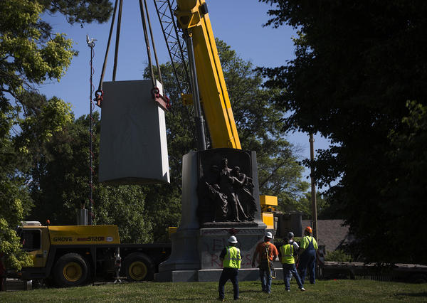 Workers remove the top half of the Confederate Memorial statue in Forest Park on Monday.