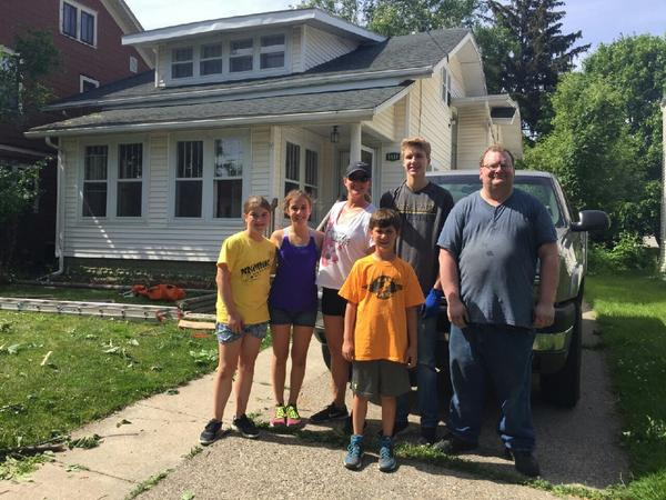 A volunteer landscaping crew stands outside LINC's first home, which will house three individuals in its pilot intentional community.