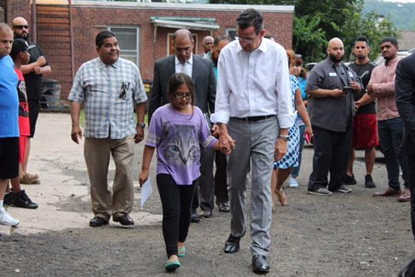 Conn. Gov. Dannel Malloy holds hands and walks with 9-year-old Hayley Chavarria outside the Iglesia De Dios Pentecostal Church in New Haven Thursday night. Chevarria's mother, Nury, was recently ordered to be deported from the United States to Guatemala.