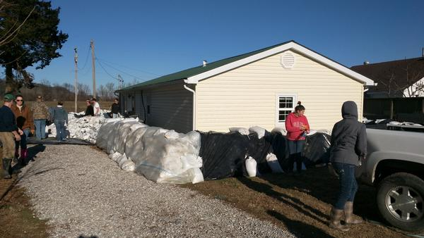 Community members in Olive Branch, Illinois barricade a neighbors home with sandbags to protect it from flood waters on Friday, Jan. 1, 2016.