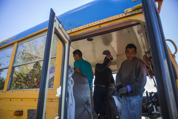 "Migrant workers board the bus that shuttles them between fields at Root Brothers Farm in Albion. ""We pay their transportation, we pay their meals on the way up, we pay their transportation home,"" said Robin Root, farm co-owner."