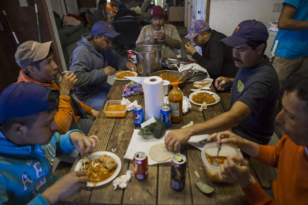 Migrant workers eat lunch together in their provided home while working at Root Brothers Farm in Albion.
