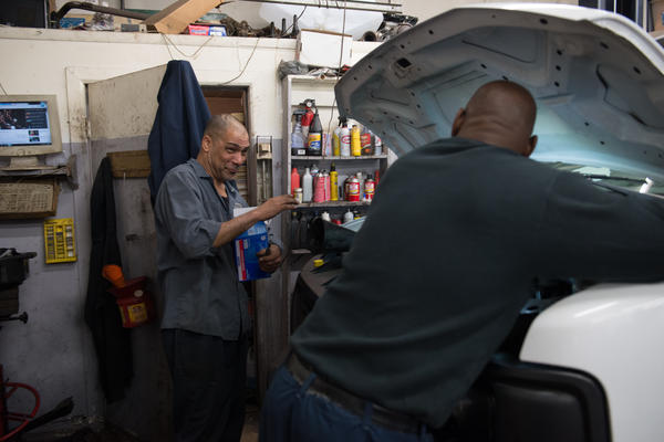 Israel Garcia jokes with his co-worker and boss, Dalbert Chambers, at Dalbert's Auto Shop. Garcia started working for Chambers with no mechanical skills and has learned everything he knows about cars through working with him for the past five years.