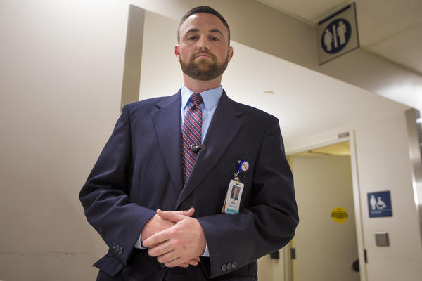 Ryan Curran, police and security operations manager at Massachusetts General Hospital, stands in front of the bathrooms in the main lobby of the hospital's lobby. (Jesse Costa/WBUR)