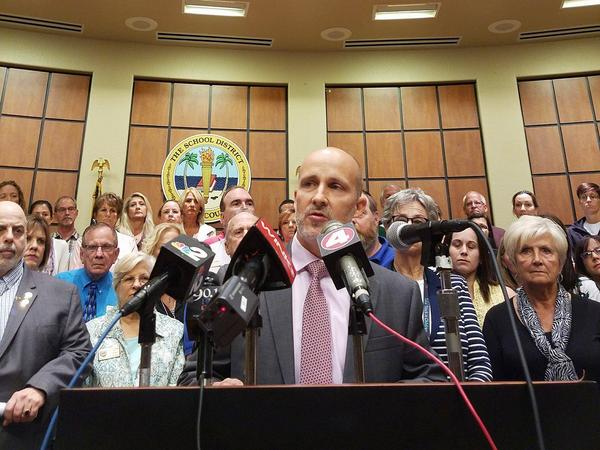 Superintendent Gregory Adkins, backed by about 50 district employees, holds a press conference