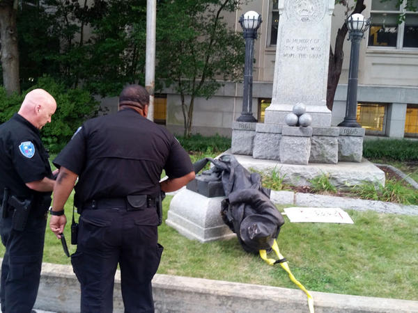 Durham police view statue of a Confederate soldier protesters in Durham Monday pulled down.