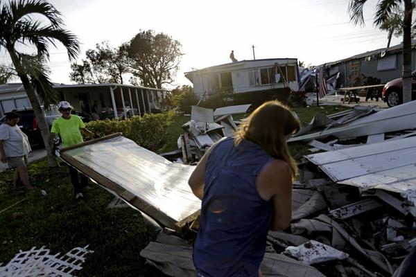 Joseph Ross, left, cleans up debris from his damaged home with help from a neighbor in the aftermath of Hurricane Irma in Naples, Fla., Sept. 13, 2017.