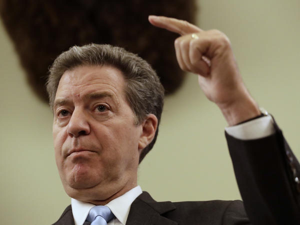 Kansas Gov. Sam Brownback talks to the media during a news conference in July.