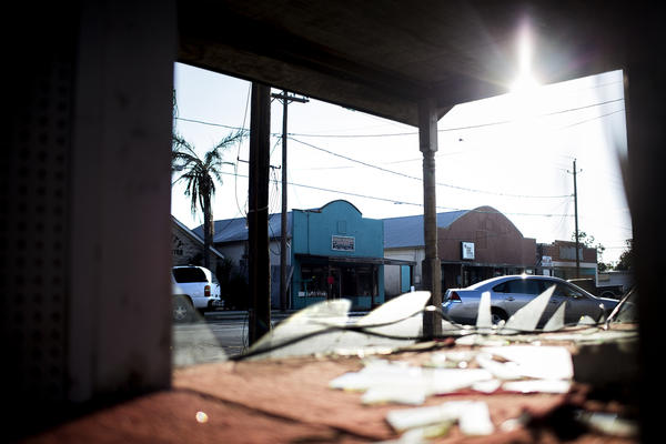 Nona's Flower Box is seen through the broken window of a nearby storefront in downtown Refugio.