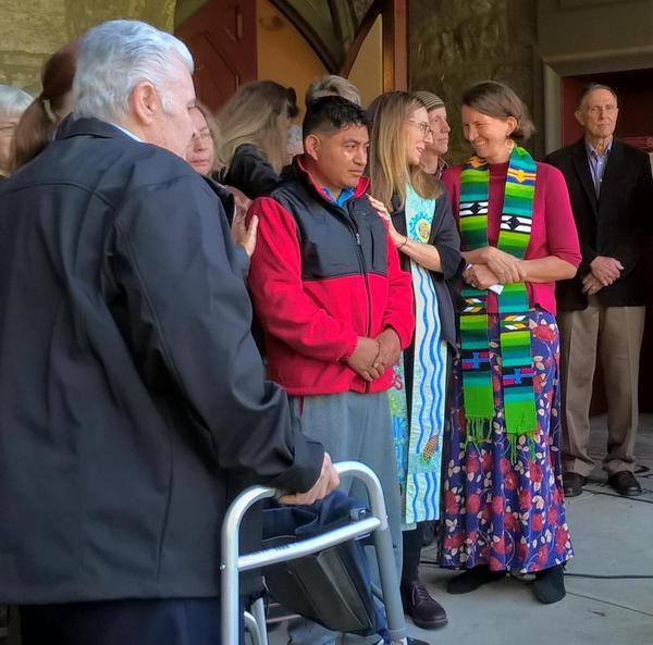 Lucio Perez, center, in a red jacket, is surrounded by local clergy in front of the First Congregational Church in Amherst, Massachusetts.