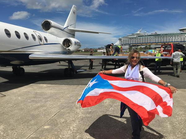 Debbie Sosa holds up a Puerto Rican flag in San Juan, before loading sick patients to fly back to Ft. Lauderdale.