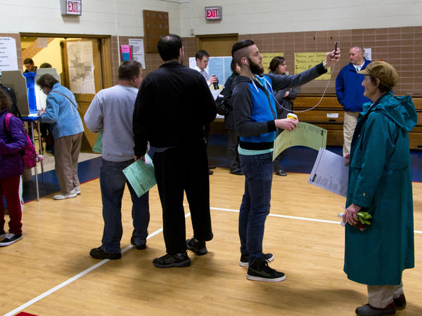 """A man takes a """"selfie"""" while waiting in line to cast his vote in the Wisconsin gubernatorial race in November."""