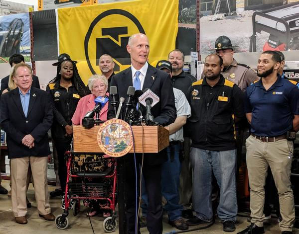 Scott flanked by Northern Tool and Equipment employees during his budget proposal announcement in Jacksonivlle Tuesday.