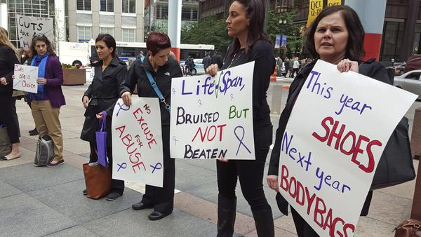A 2015 protest by advocates for victims of domestic abuse takes place outside state offices in downtown Chicago. The protests were sparked by a lack of funding for domestic violence shelters due to the state's budget crisis.