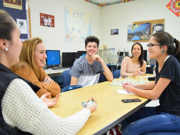 Mohawk Club adviser Robin Logan (in back) watches as club members Amanda Rourke (from left), Keely Thompson-Cook, Landon Laffin and Mallory Sunday discuss their high school's Native American Day celebration.