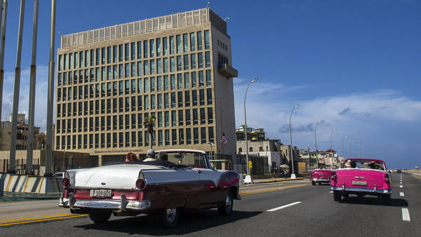 Tourists ride classic convertible cars on the Malecon beside the United States Embassy in Havana, Cuba.