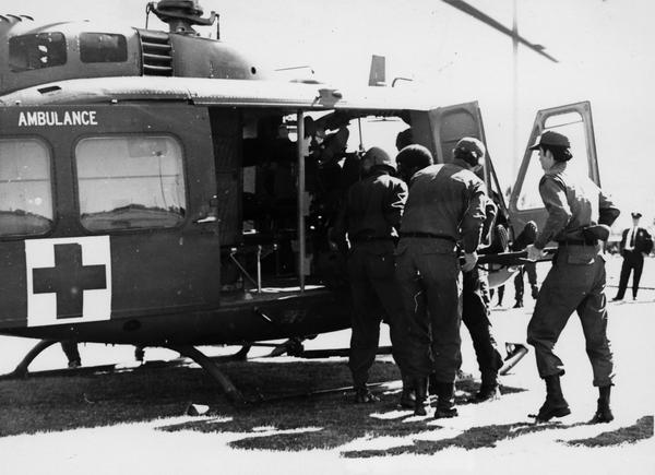 A San Antonio-based MAST crew loads a patient onto a medevac helicopter around 1970. The MAST program was designed to bring battlefield emergency medical techniques to civilians in the U.S.
