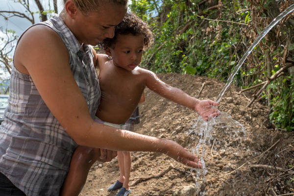 Paola Bernacett carries one-year-old Darian Santos as he touches water piped from a stream to a Utuado, Puerto Rico roadside. The stream water may be contaminated with bacteria.