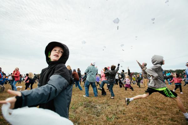Children scramble to catch candy attatched to parachutes and dropped from a World War II era aircraft during an event in Manteo, N.C., on Sunday, Dec. 17, 2017.