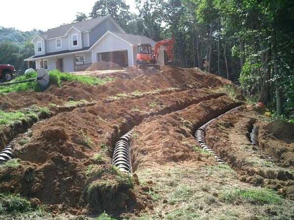 Septic system installation underway for a home on steep slopes.