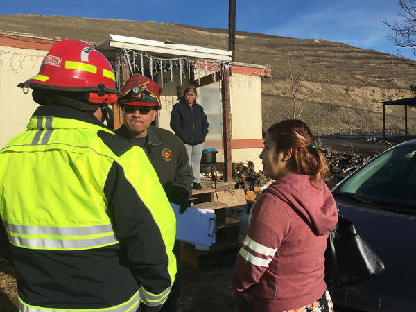 Yakima Valley firefighters talk with farmworker families, trying to persuade them to move away from a developing landslide near Union Gap, Wash.