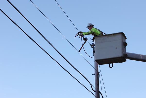 Steve Music works to replace a power line damaged by Tropical Storm Irene in Buxton in Aug. 2011.