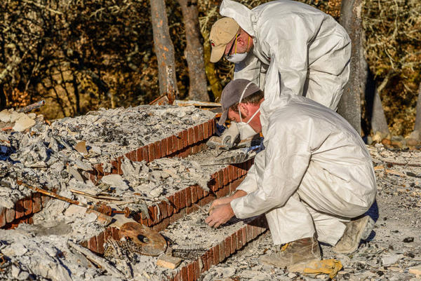 Alex DeGeorgey (left) and Mike Newland survey the search area of Lampi's home after the dogs narrowed the location of where Lampi's mother's ashes were likely to be found. They use delicate archaeological digging methods to recover the ashes without disturbing them.