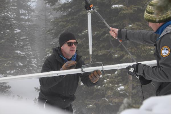 Natural Resources Conservation Service snow surveyors Mike Ardison (left) and Karl Wetlaufer use an aluminum tube to take manual measurements of snowpack on Colorado's Berthoud Pass.
