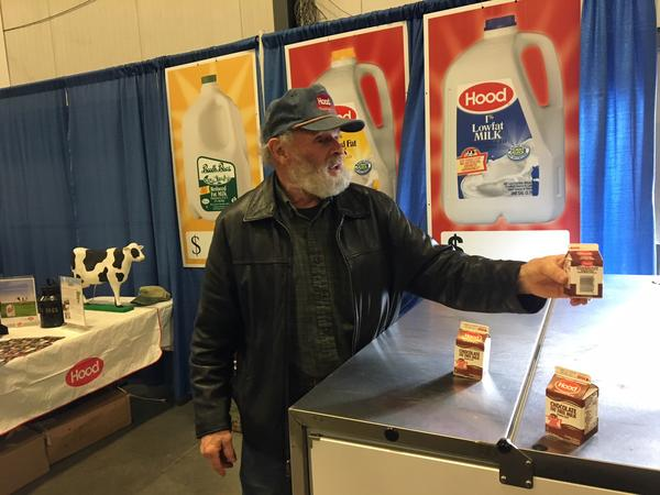 Randolph Center farmer David Silloway offers free milk samples at the annual Farm Show. An oversupply of organic milk has stalled Silloway's plans to earn a higher price for his product.