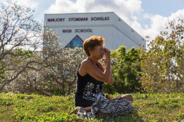 A woman wipes her face as she mourns in front of Marjory Stoneman Douglas High School in Parkland. The school will begin a phased reopening today.