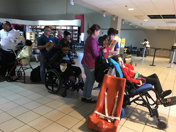 A group of evacuees waits to get on the plane chartered by the Puerto Rico Recovery Alliance to fly back to the mainland.