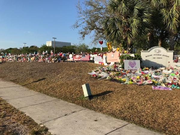 The memorial including flowers, stuffed animals, signs and photographs outside Marjory Stoneman Douglas High School in Parkland keeps growing.