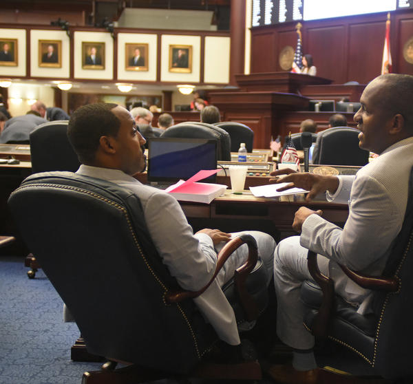 Reps. Ramon Alexander and Bobby DuBose confer on the House floor. Members of the chamber's black caucus said they felt like they were silenced during the debate over guns, despite that gun violence affects their communities often.