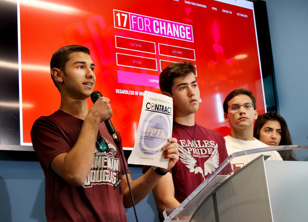 Adam Buchwald, 16, left, and Zach Hibshman, 16, right, juniors at Marjory Stoneman Douglas High School, created a contract for those who are not old enough to vote, where their parents and other guardians can sign and promise to vote for gun reforms.