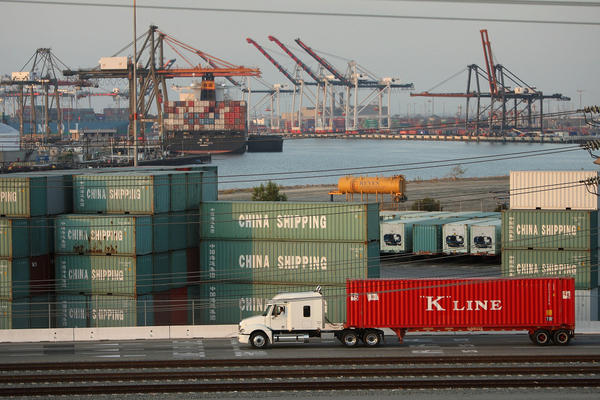 A truck passes shipping containers at China Shipping at the Ports of Long Beach and Los Angeles, the busiest port complex in the U.S., near Long Beach, Calif. Stricter emissions standards have cut down on air pollution from the trucks, which has been one of the most significant sources of air pollution in California for many years.