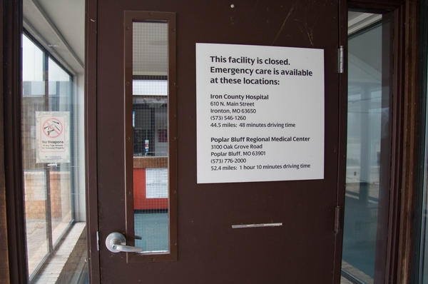 A sign on the door of the shuttered hospital in Ellington, Missouri lists the nearest facilities with functional emergency rooms and how far away they are by car.